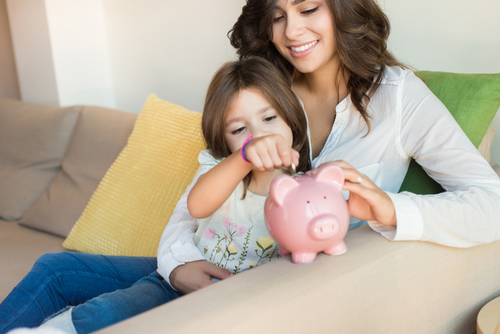Mom and daughter putting money in piggy bank